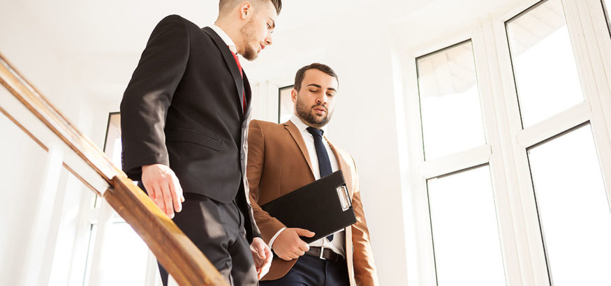 Business partners in suit walking and talking on the stairs of an office building
